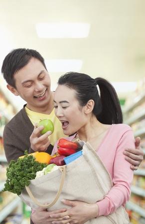 woman apple: Man Feeding Woman Apple in Grocery Store