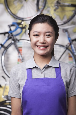 Portrait of young female mechanic in bicycle store, Beijing photo