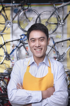 Portrait of young male mechanic in bicycle store, Beijing photo