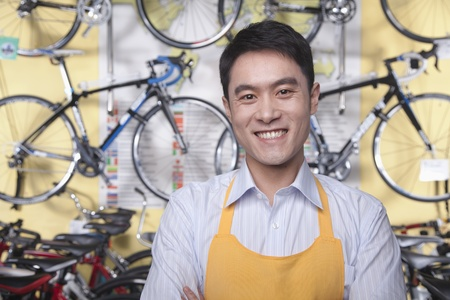 small business: Portrait of young male mechanic in bicycle store, Beijing