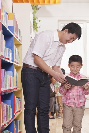 Father and Son Looking at a Book Together Stock Photo