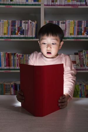 Boy Surprised By Glowing Book photo