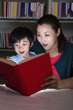 Boy and Teacher Surprised By Glowing Book photo