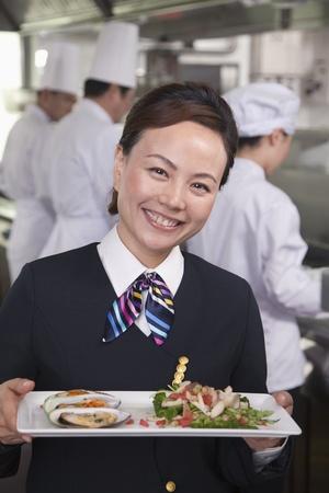 Restaurant Hostess Presenting Gourmet Dish photo