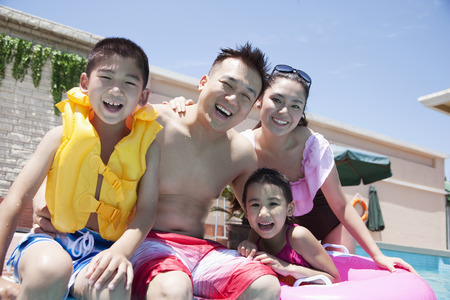 Family portrait, mother, father, daughter, and son, smiling by the pool  photo