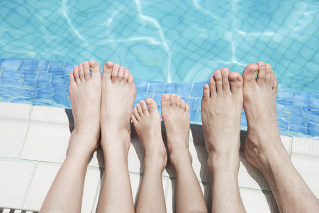 Close up of three peoples legs by the pool side Stock fotó