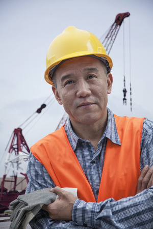 protective workwear: Portrait of proud worker with arms crossed in protective workwear outside in a shipping yard, crane in the background