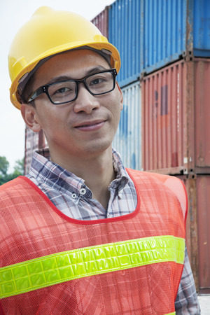 Portrait of smiling young engineer in protective workwear outdoors in a shipping yard photo