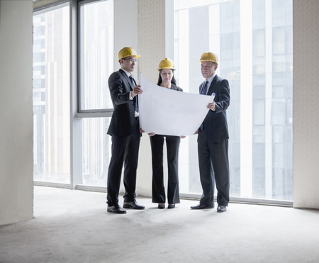 Three architects in hardhats examining a blueprint in an office building Stock Photo
