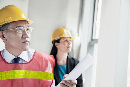 Two architects in protective workwear and hardhats working in an office building Stock Photo