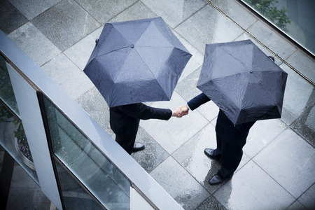 social grace: High angle view of two businessmen holding umbrellas and shaking hands in the rain
