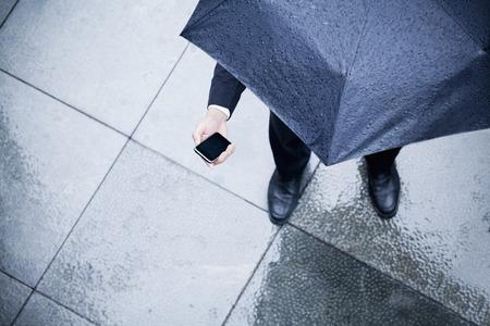 UOMO pioggia: Elevato angolo di visione di imprenditore in possesso di un ombrello e guardando il suo telefono sotto la pioggia