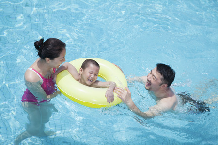 three day beard: Smiling happy family playing in the pool with their son in an inflatable tube