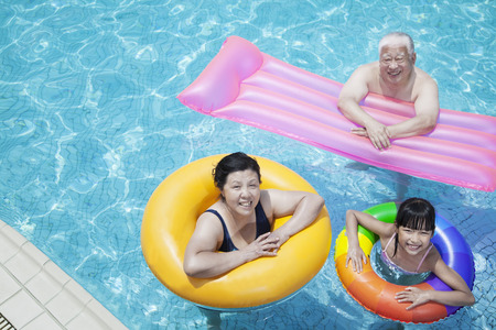 Multi-generational family playing in the pool with inflatable tubes, looking at camera photo
