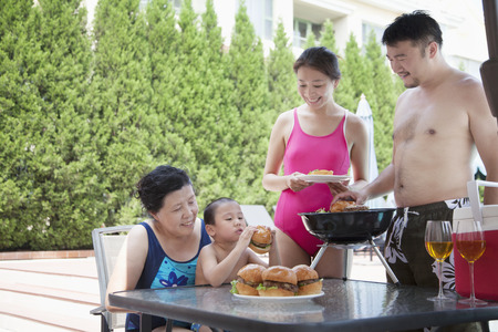 barbequing: Smiling multi-generational family barbequing by the pool on vacation Stock Photo