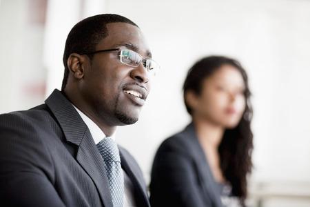 ビジネス会議でリッスンしている実業家の笑みを浮かべてください。