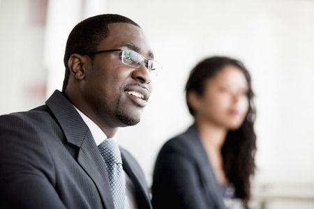 african business man: Smiling businessman listening at a business meeting