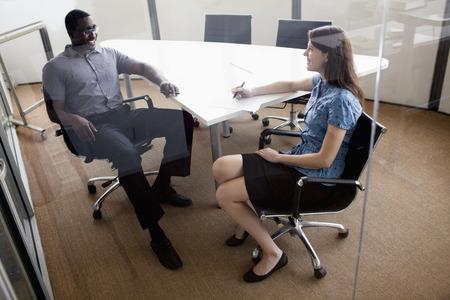 dos personas hablando: Dos hombres de negocios sentado en una mesa de conferencias y discuten durante una reunión de negocios