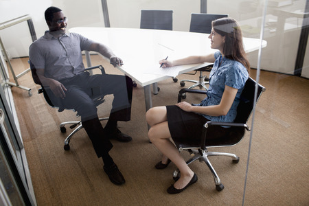 Two business people sitting at a conference table and discussing during a business meeting Stock Photo