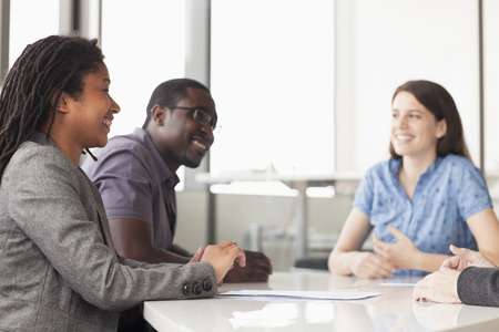 board room: Three business people sitting at a conference table and discussing during a business meeting