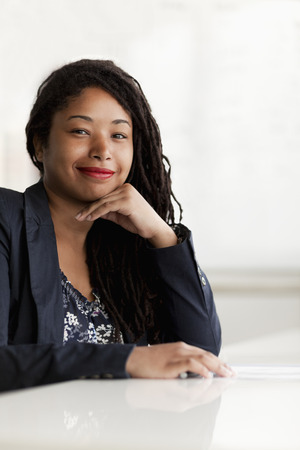 Portrait of smiling businesswoman with dreadlocks, head and shoulders Stock Photo