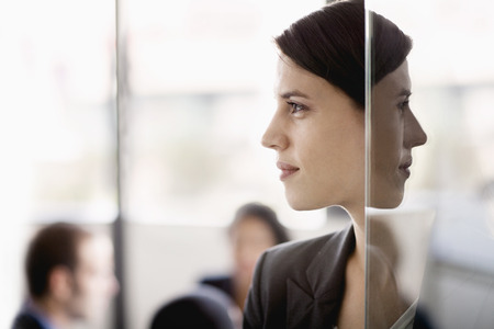 reflection: Side profile on a businesswoman with coworkers in the background