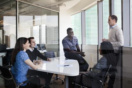 sala de reuniones: Cinco personas sentadas en una mesa de conferencias y discuten durante una reuni�n de negocios