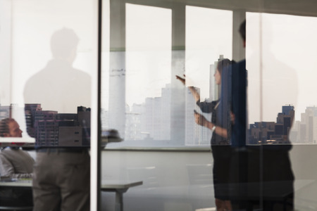 corporate meeting: Four business people standing and looking at a white board on the other side of a glass wall Stock Photo