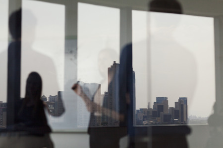 other side of: Three business people standing and looking at a white board on the other side of a glass wall Stock Photo
