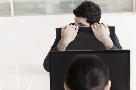 Tired businessman holding his computer monitor and resting photo