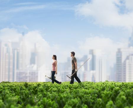 Zwei junge Menschen tragen Gartengeräte zu Fuß über einer grünen Wiese mit Pflanzen, Großstadt im Hintergrund Lizenzfreie Bilder