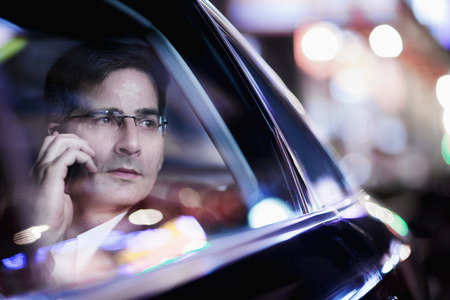Businessman on the phone and looking out the car window at night, reflected lights