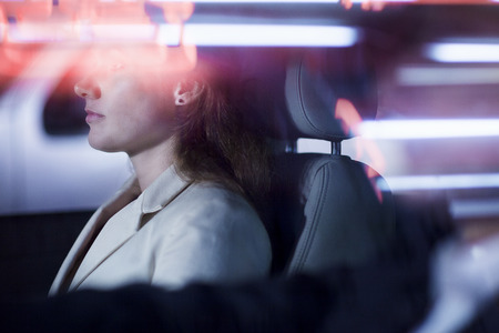 night city: Serene businesswoman sitting in the car at night, illuminated and reflected lights on the car window