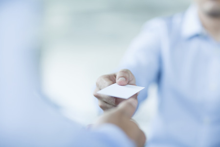 business card in hand: Close up of two businessmen exchanging business cards Stock Photo