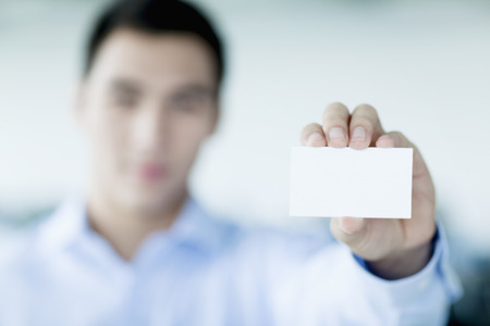 holding business card: Young businessman holding business card to the camera