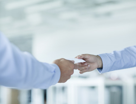 hand business card: Close up of two businessmen exchanging business cards Stock Photo
