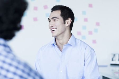 Two young businessman laughing and talking in the office photo