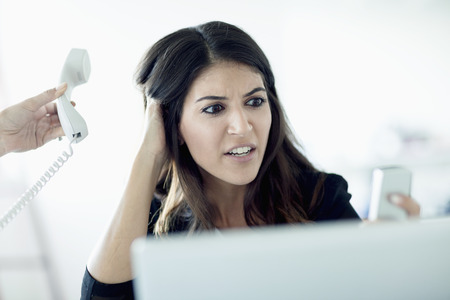 answering: Overworked young businesswoman answering phones Stock Photo