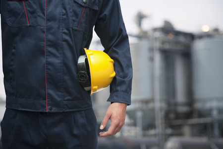 Midsection of young worker holding a yellow hardhat  outdoors with factory in the background