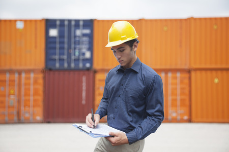 Smiling young engineer in protective work wear in a shipping\ yard examining cargo and writing on clipboard
