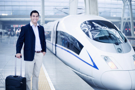Businessman standing with a suitcase on the railroad platform by a high speed train in Beijing photo