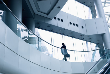 office space: Distant businessman walking in a modern office building