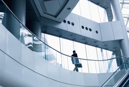empleado de oficina: Distante empresario caminando en un moderno edificio de oficinas