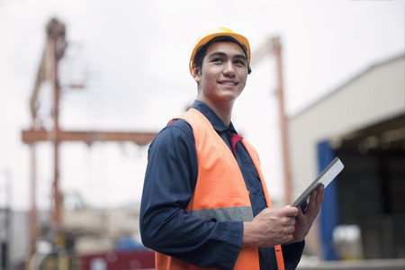 white collar worker: Proud young worker in protective work wear in a shipping yard