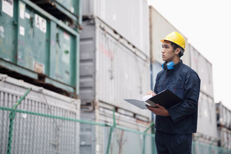 protective work wear: Young worker in protective work wear examining cargo in a shipping yard