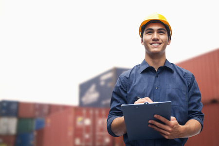 protective work wear: Smiling young engineer in protective work wear in a shipping yard examining cargo