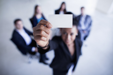 business strategy: Businesswoman holding a business card up to the camera- Shannon Fagan Photography