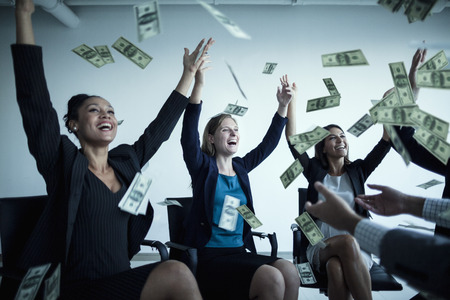Business people with arms raised throwing money in the air