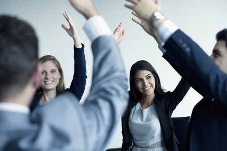 Business people cheering with arms in the air Stock Photo