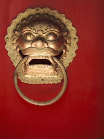Close-up of ornate gold door knocker on red door Stock Photo
